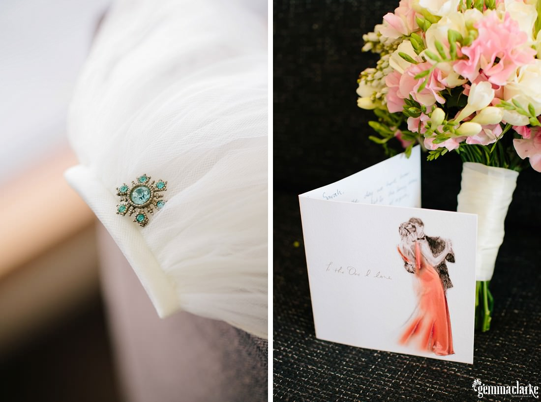 A brooch attached to a veil, and a card next to a bouquet
