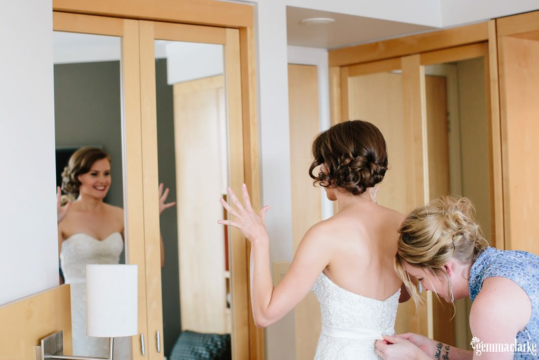 A bride looking happily into a mirror as the back of her bridal gown is fastened