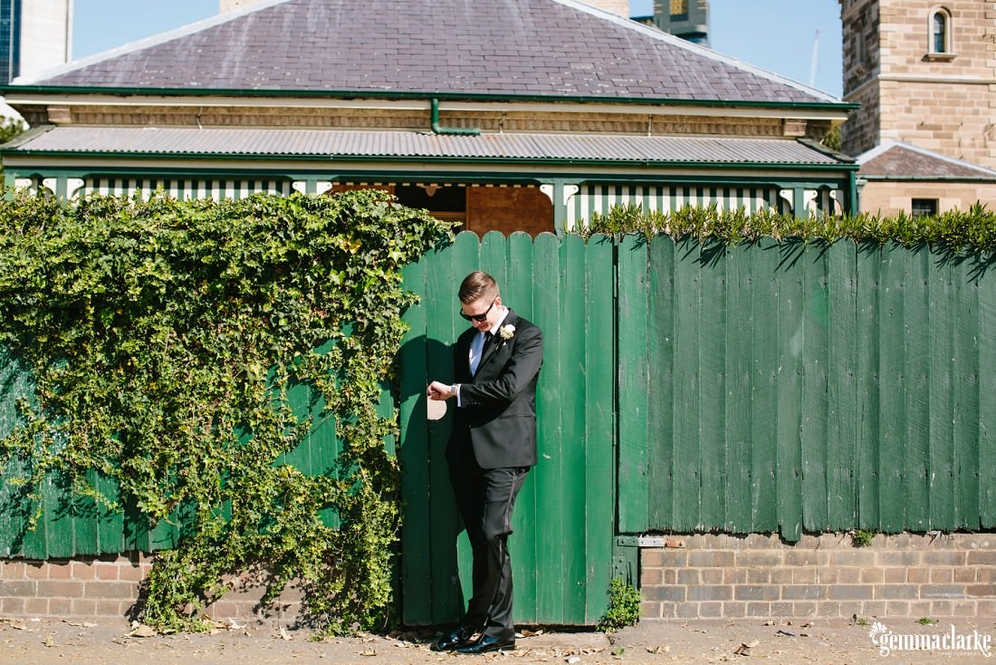 A groom standing in front of a green wooden fence checking his watch