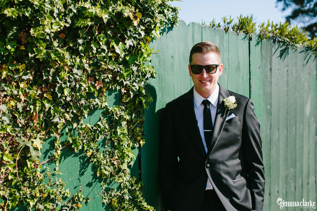 A groom in a dark suit and sunglasses smiling and leaning against a green wooden fence