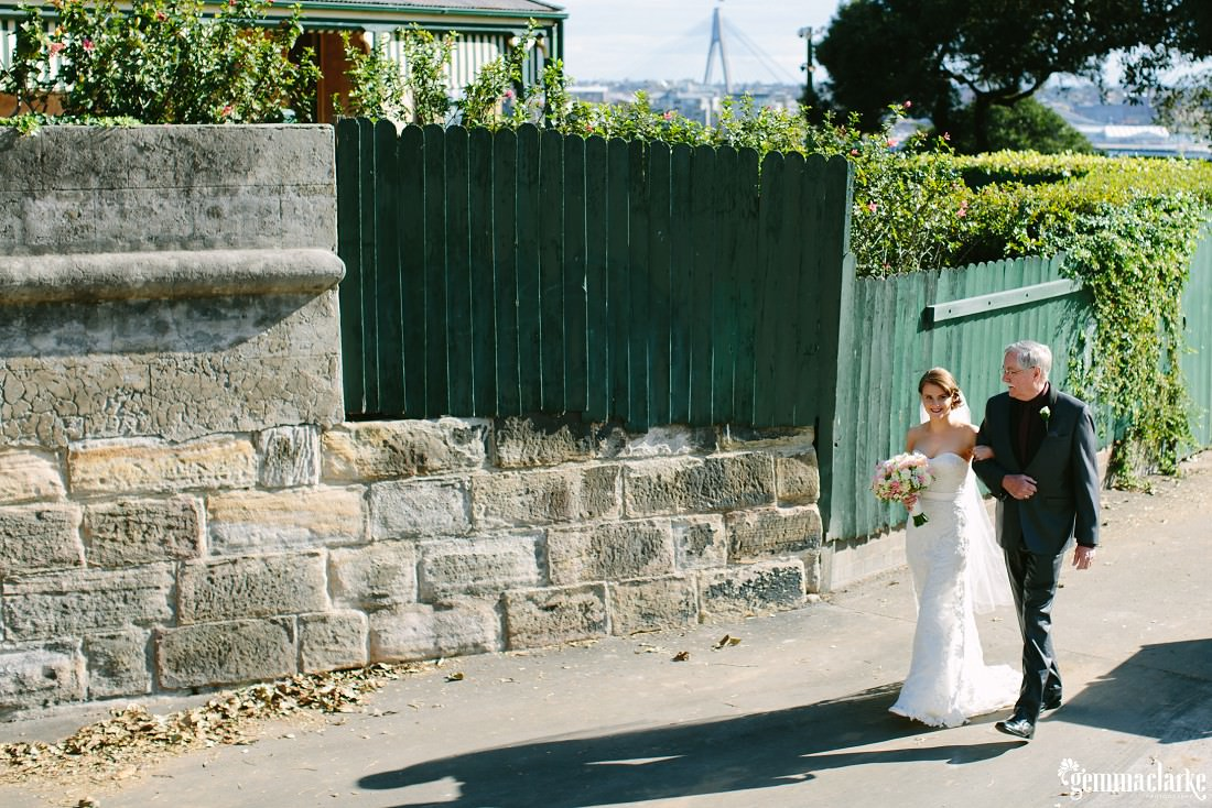 A bride walking along a path, arm in arm with her father