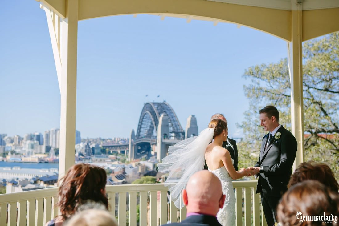A bride and groom holding hands during their ceremony with the Sydney Harbour Bridge in the background
