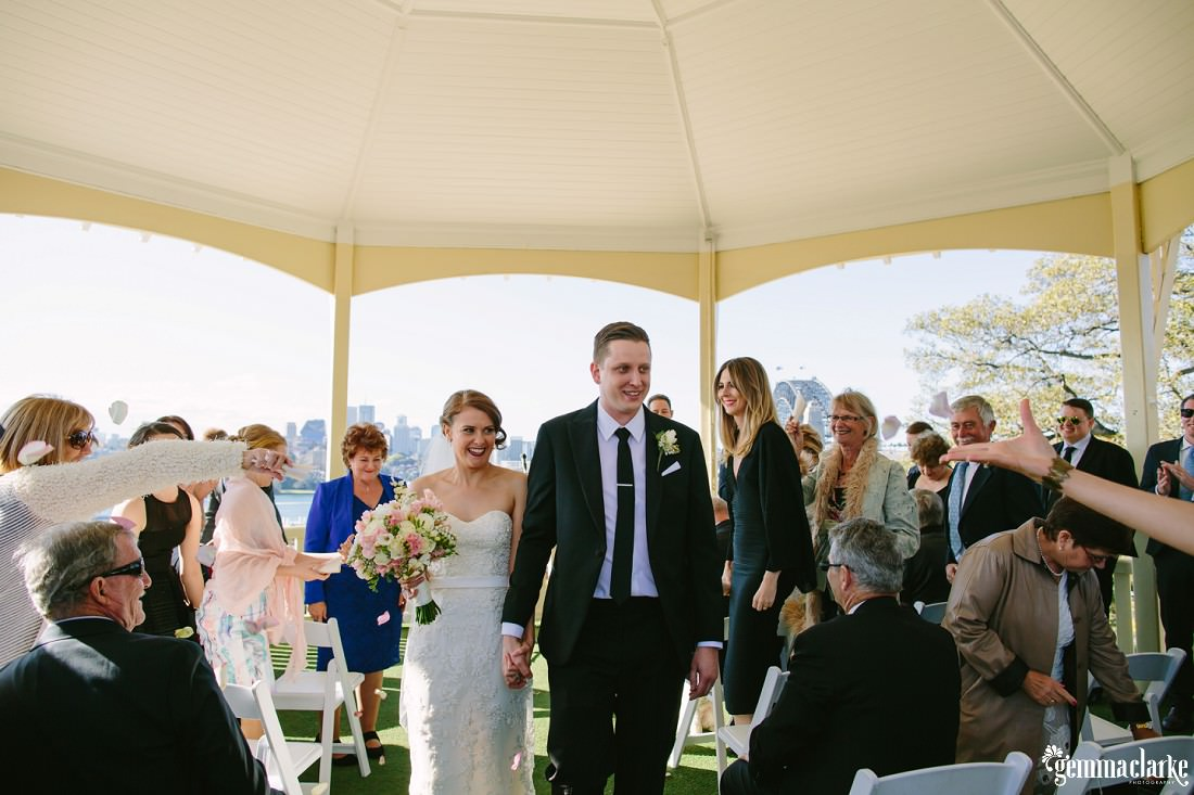 A smiling bride and groom being congratulated as they walk back down the aisle after their wedding ceremony