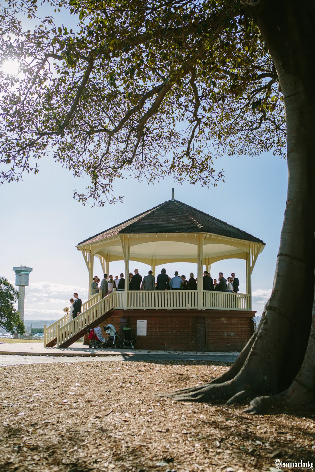A bride and groom walk down the hill of the gazebo at Observatory Hill in Sydney after their wedding ceremony