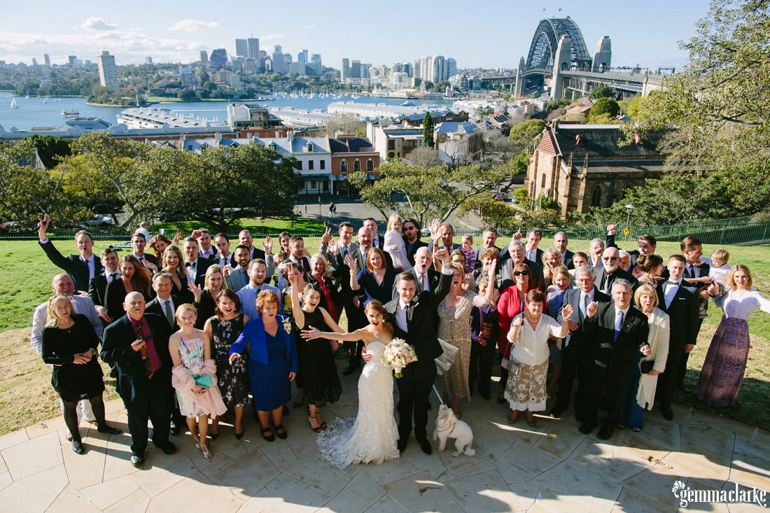 A group photo of a bride and groom and their wedding guests on Observatory Hill in Sydney