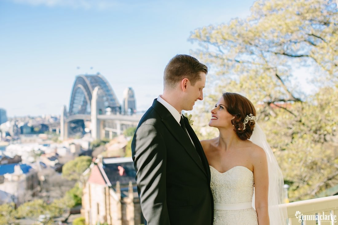 A smiling bride and groom standing close and looking lovingly into each others eyes with Sydney Harbour Bridge in the background