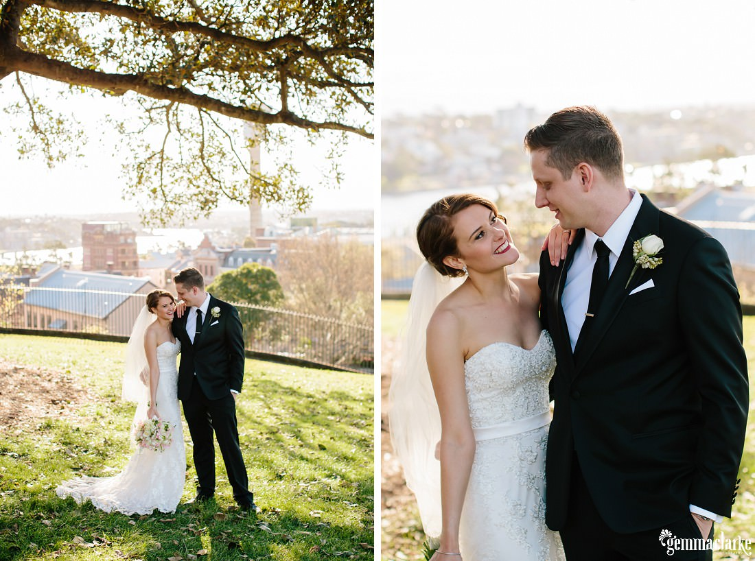 A smiling bride with her arm on her groom's shoulder as they stand under a tree on a hill