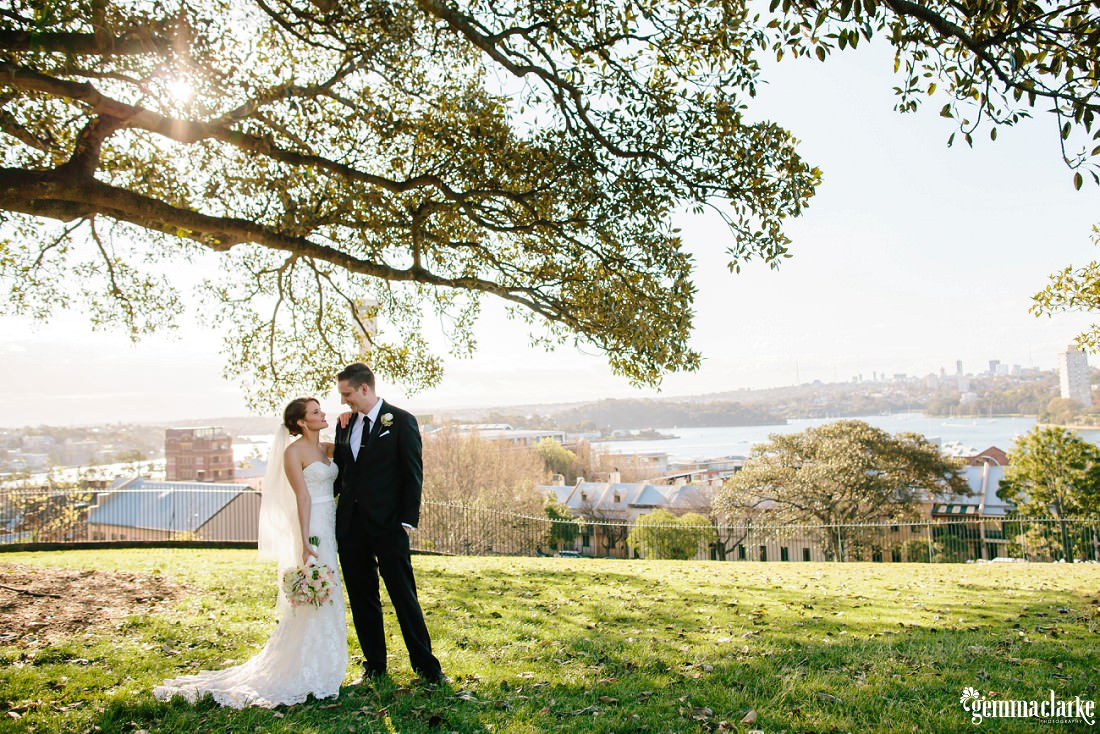 A smiling bride with her arm on her groom's shoulder as they stand under a tree on a hill with Sydney Harbour in the background
