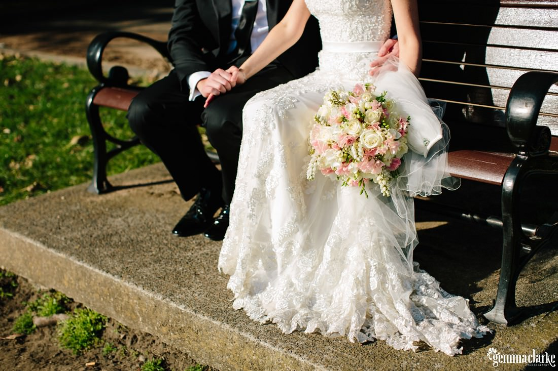 A bride and groom holding hands and sitting on a wooden park bench