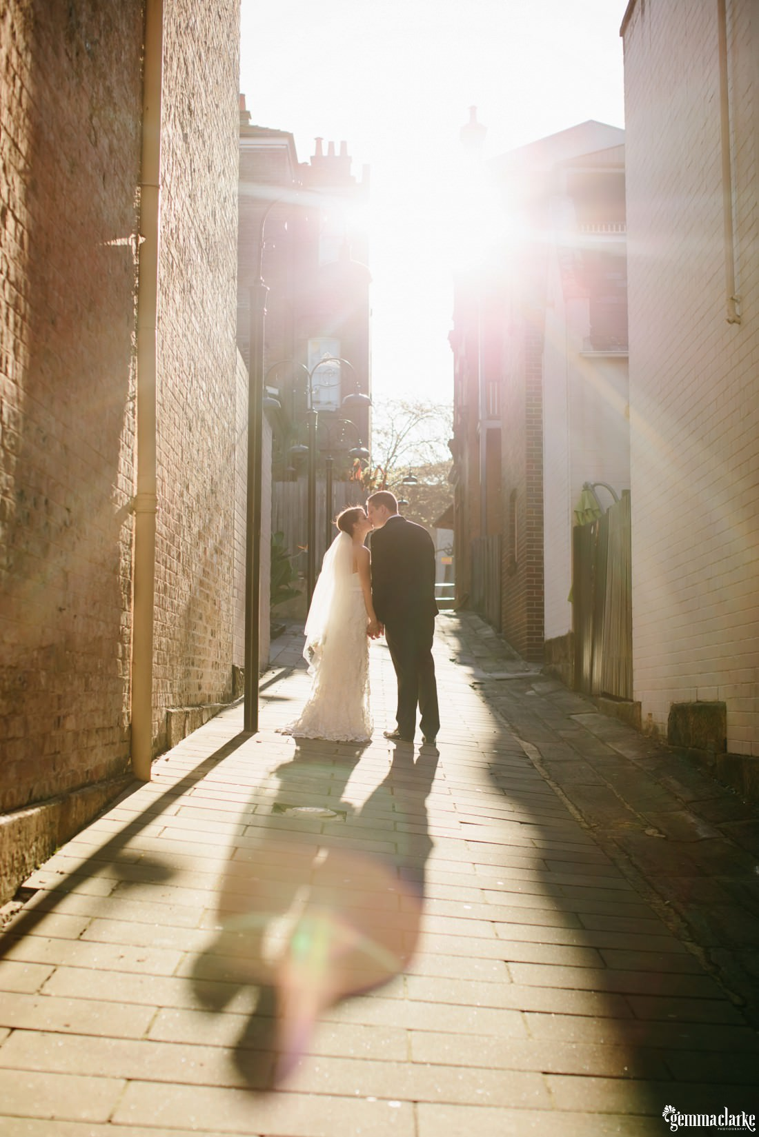 A bride and groom kissing in an alley way with the sun streaming in behind them