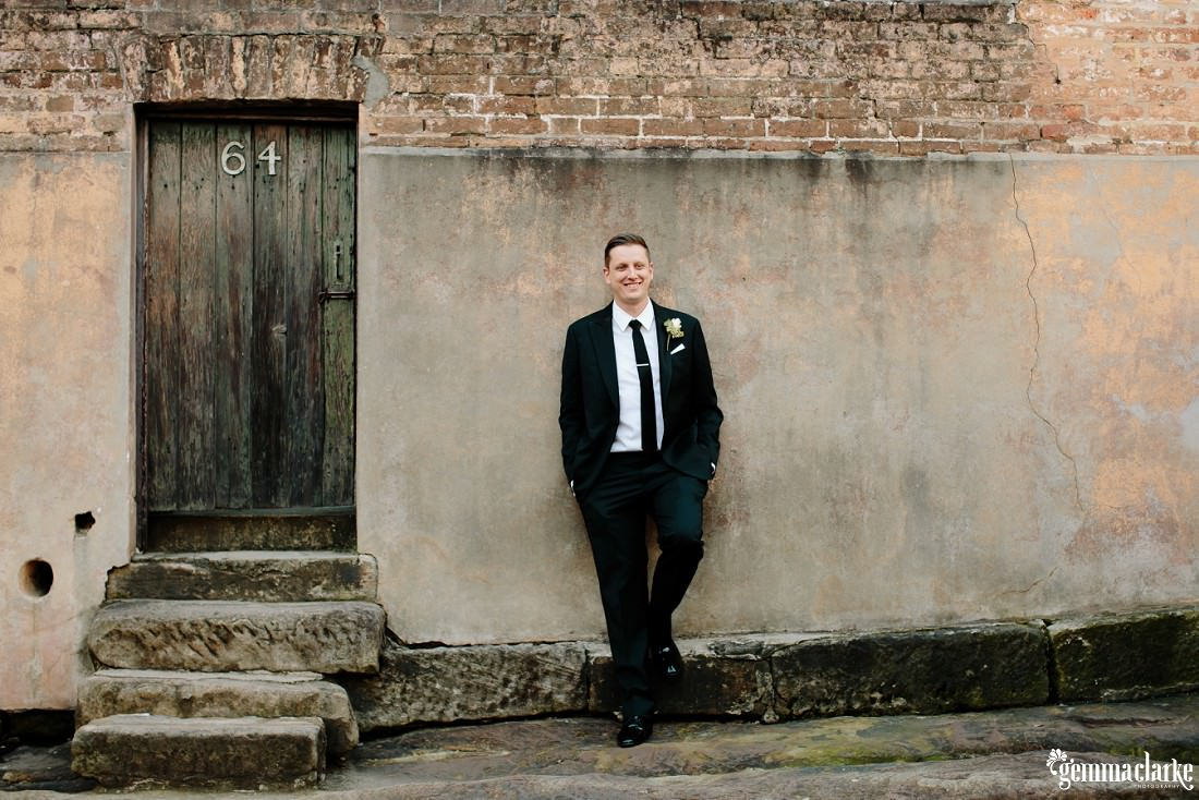 A groom with his hands in his pockets smiling and leaning back against a stone wall