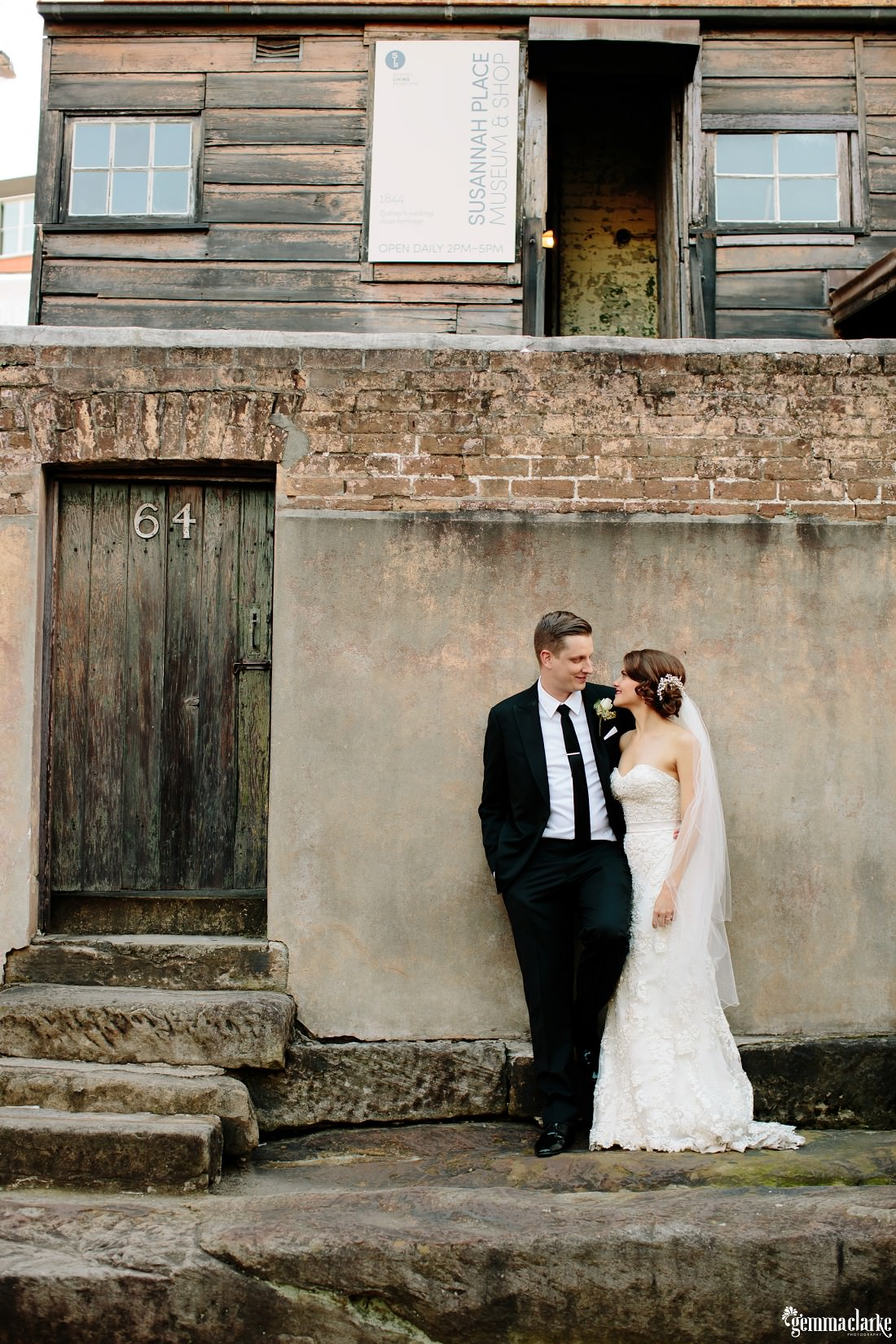 A bride and groom standing close and looking into each others eyes as they stand in front of a stone wall in an alley way