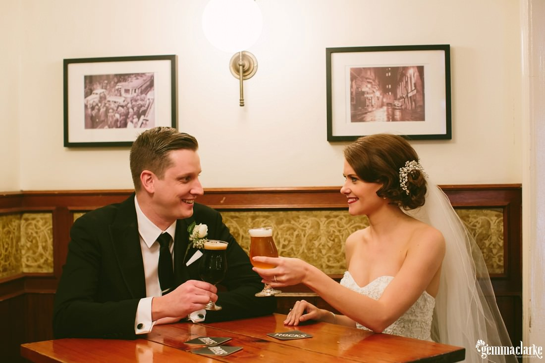 A smiling bride and groom sitting in a pub, about to clink beer glasses together