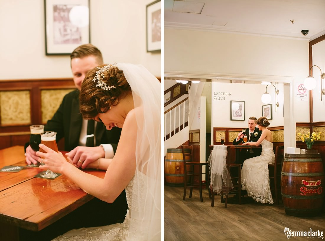A bride and groom sitting at a table in a pub, laughing and having a beer