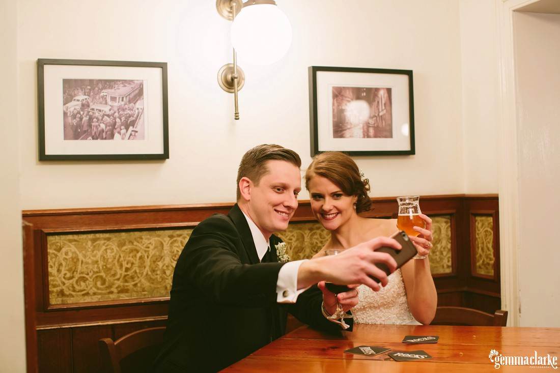 A groom taking a selfie of he and his bride as they sit in a pub having a beer