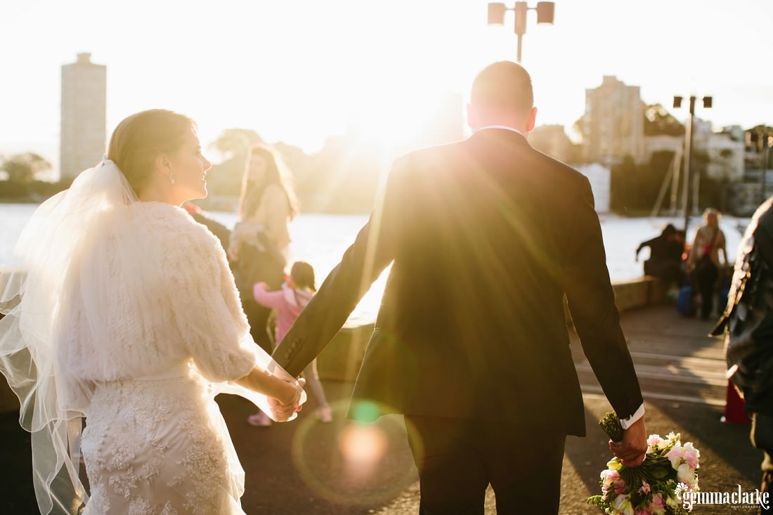 A bride and groom holding hands and walking along a wooden pathway near Luna Park