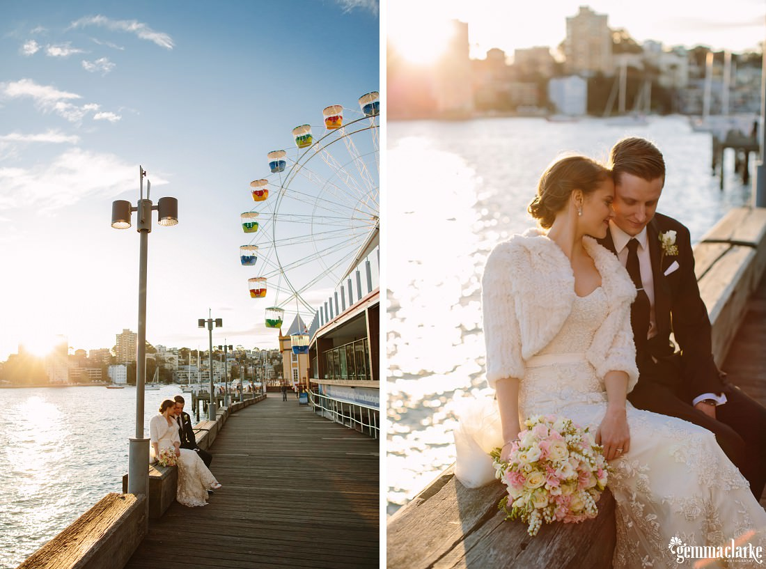 A bride and groom sit together on a wooden beam near the water with the Ferris wheel from Luna Park in the background