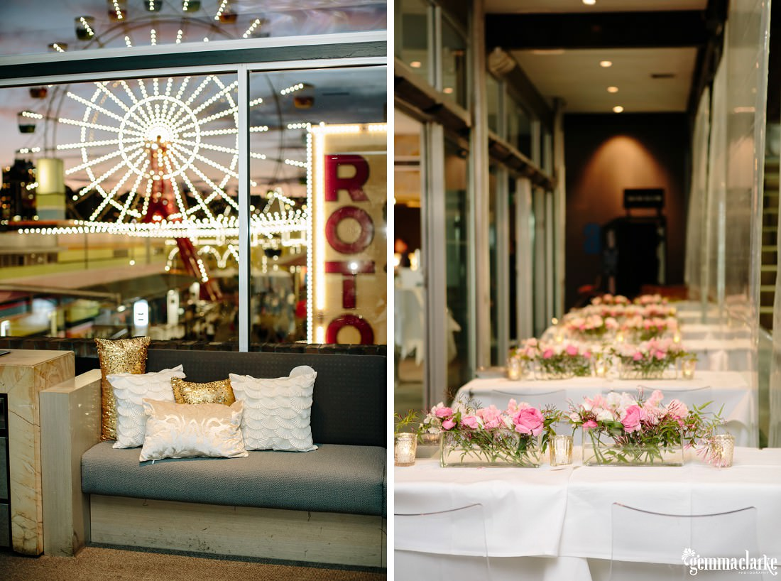 A reception setup with white tables, clear backed chairs and floral decorations, and a couch with cushions in front of a window with the lit up Ferris wheel from Luna Park in the background