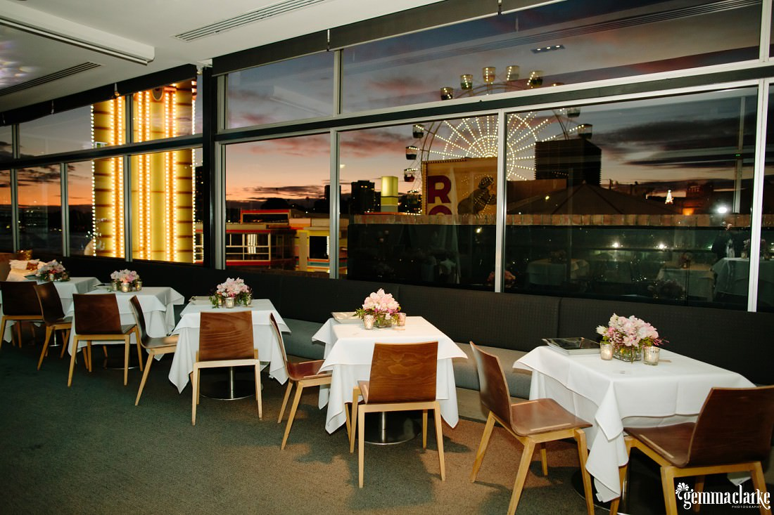 A wedding reception setup with brown chairs, white tables, floral decorations, and the Ferris wheel from Luna Park through a window in the background
