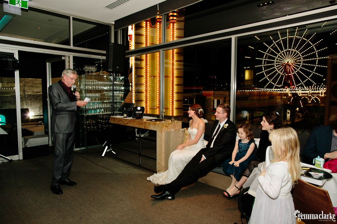 A bride and groom and wedding guests look on as the bride's father delivers a speech
