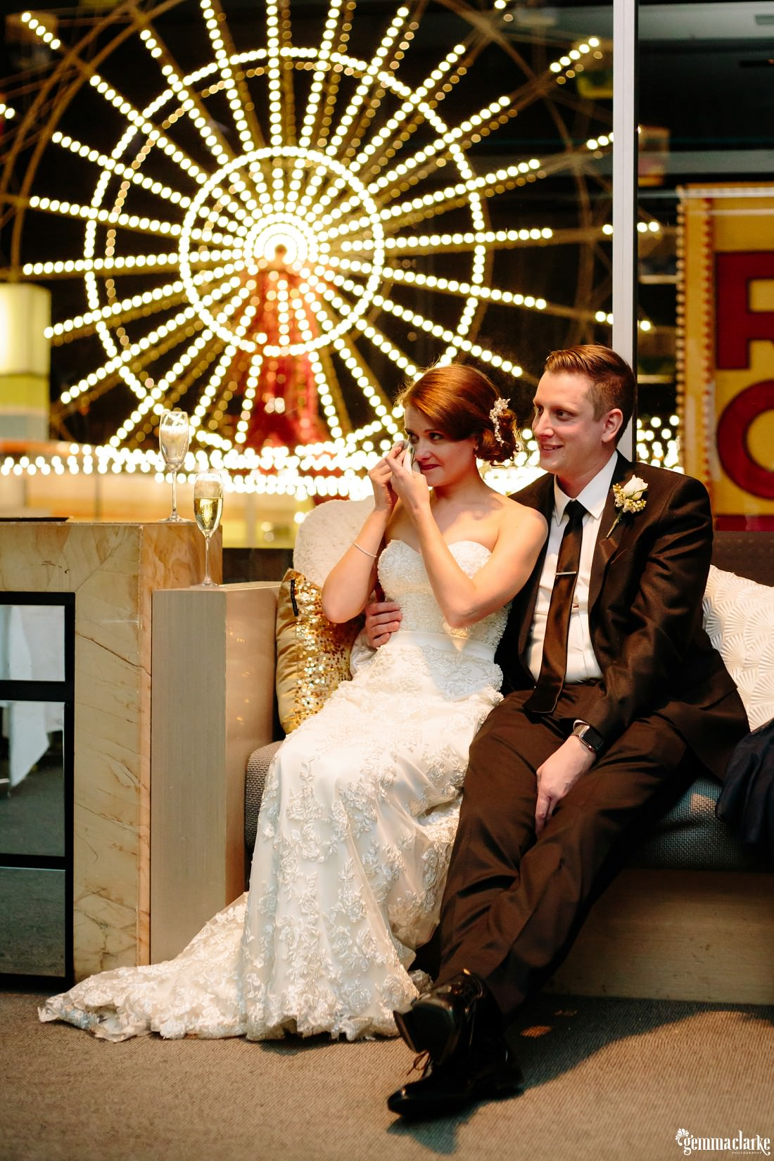 A bride wipes a tear from her eye as her groom holds her close, with the Luna Park Ferris wheel behind through the window