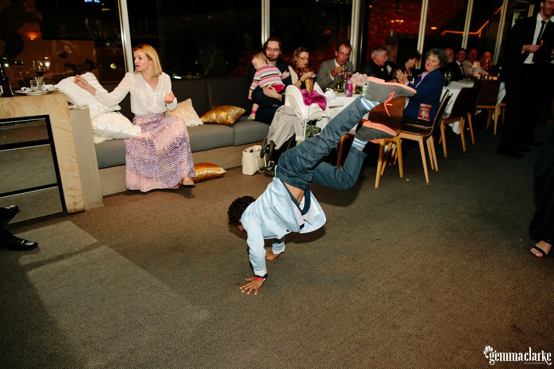 A young boy busting a move on the dance floor as wedding guests look on