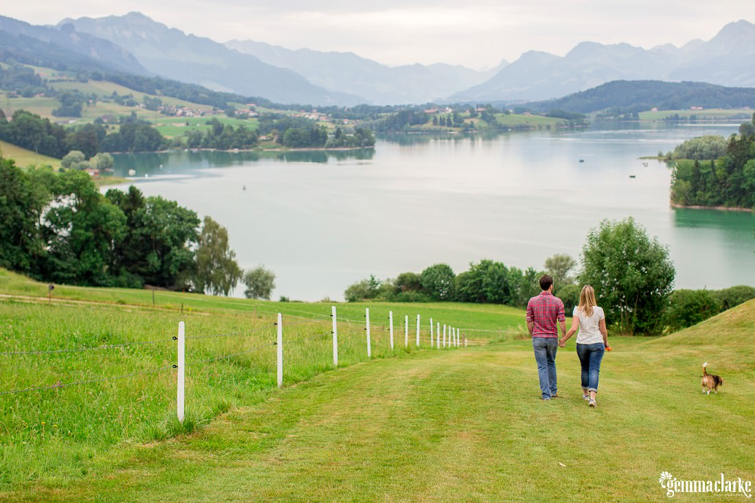 A man and woman hold hands walking down a hill with their dog, toward a lake surrounded by mountains - Lifestyle Portraits in Switzerland