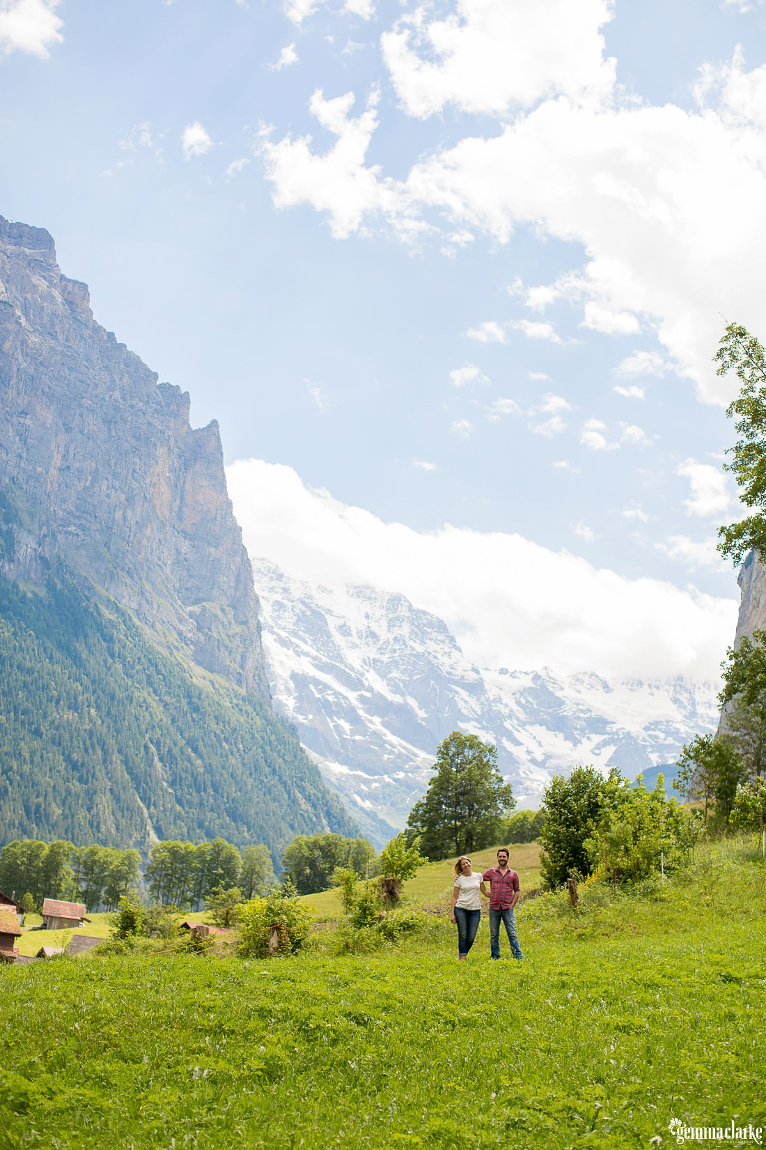 A man and woman with an arm around each other standing in a valley surrounded by mountains - Lifestyle Portraits in Switzerland