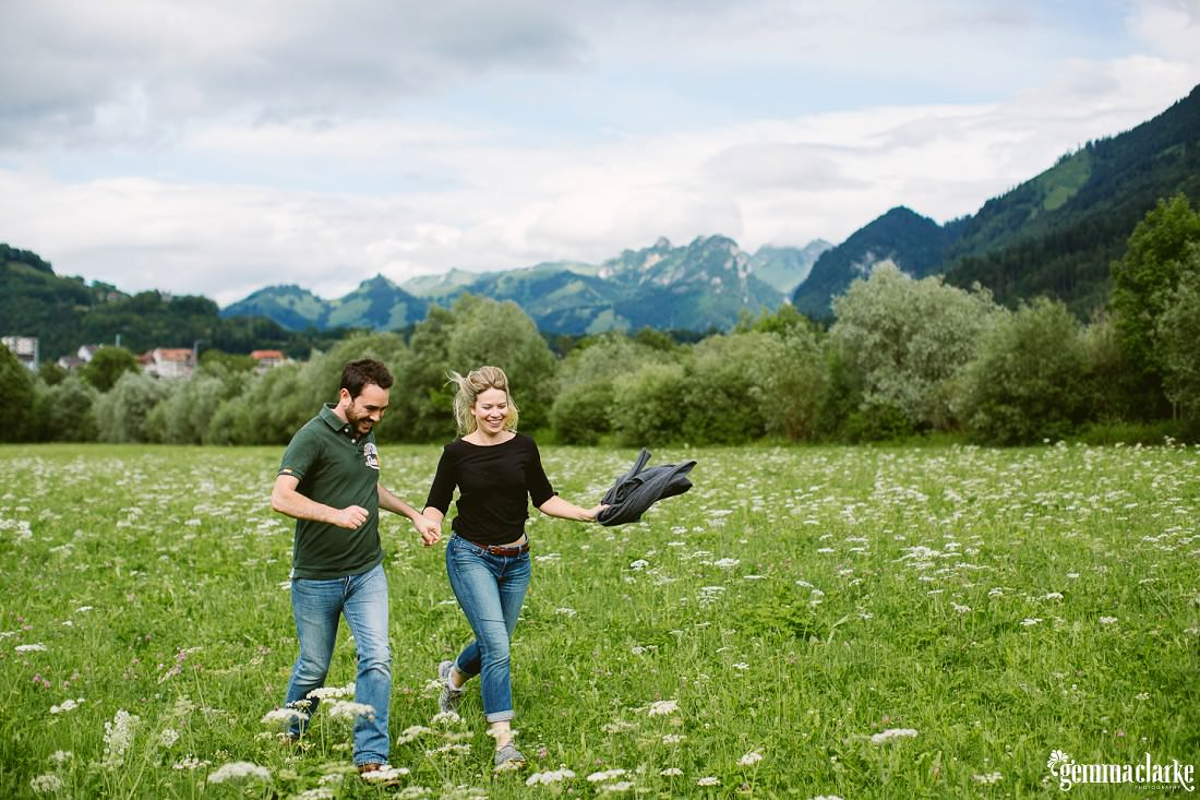 A man and woman holding hands running through a grassy field - Lifestyle Portraits in Switzerland