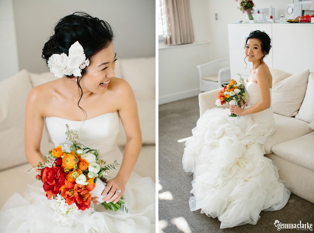 A bride poses on a white couch in her white gown with beautiful white, orange and red bouquet - Simmer on the Bay Wedding