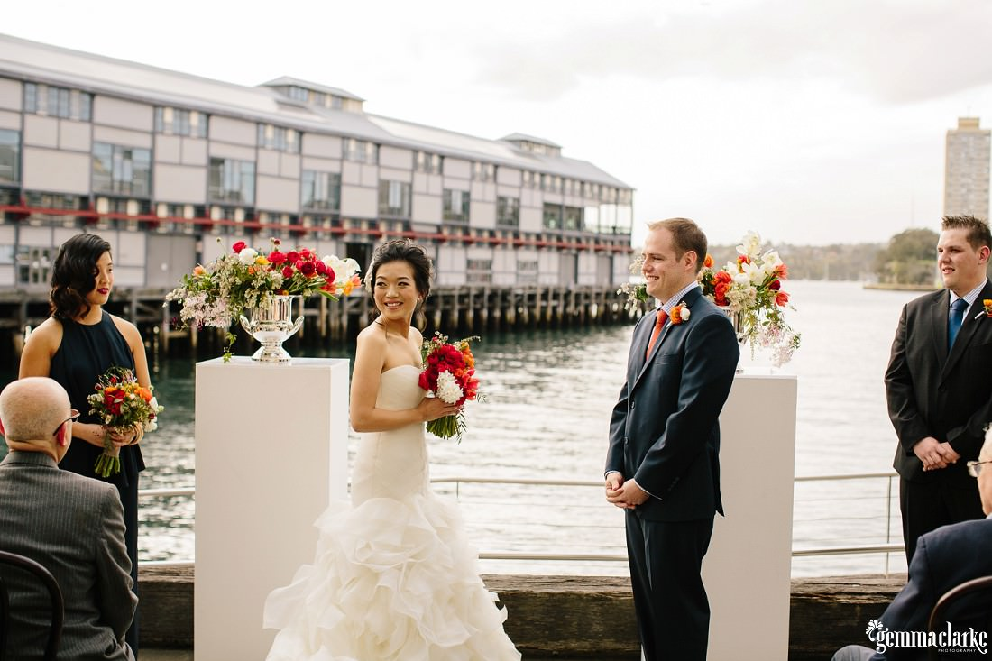 A bride and groom at their ceremony by the water in Sydney - Simmer on the Bay Wedding
