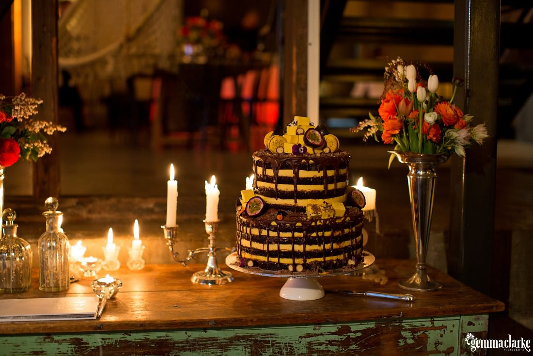 A yellow wedding cake with chocolate drizzle and passionfruit slices - Simmer on the Bay Wedding