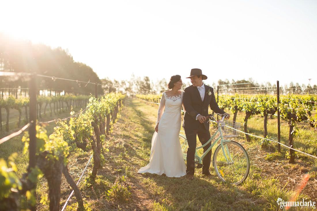 Bride and groom posing in a vineyard with a vintage bicycle - Robert Oatley's Vineyard Wedding