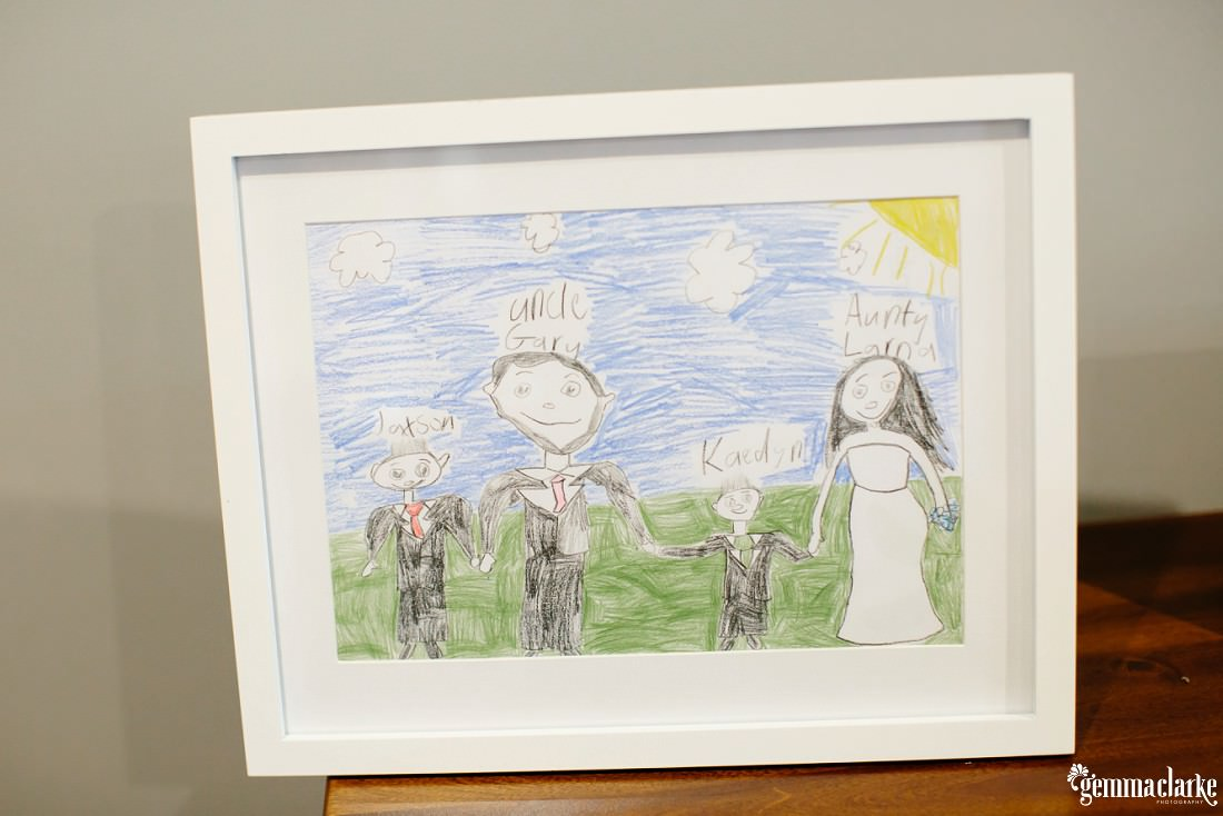 A child's drawing of two adults and two children all holding hands in a white frame