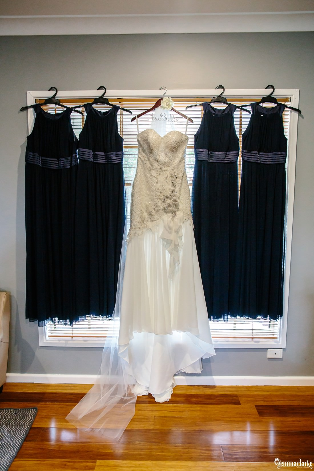 An off white bridal gown and four navy bridesmaids dresses on hangers, hanging in a window