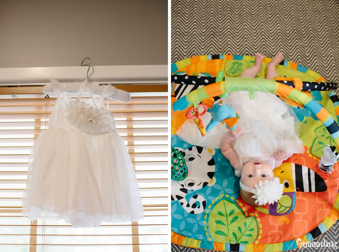 A white baby's dress on a hangar, and then a baby wearing the dress and laying on a colourful mat