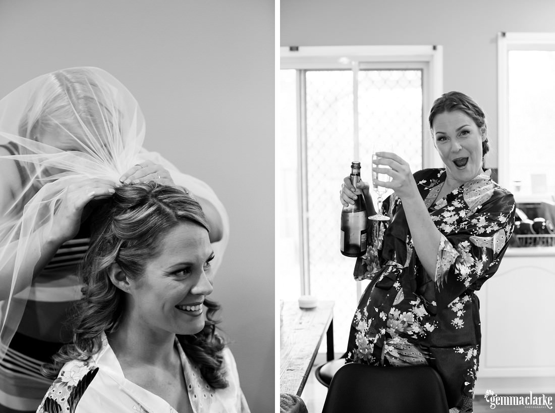 A smiling bride having her veil attached to her hair and a bridesmaid with a bottle and glass of champagne