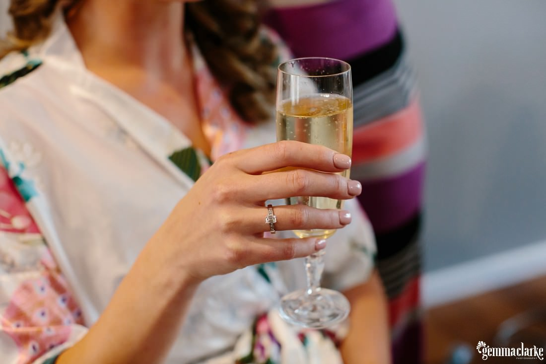 A close up of a bride's hand holding a glass of champagne