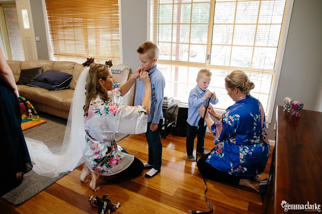A bride and a bridesmaid helping two young boys into their wedding attire