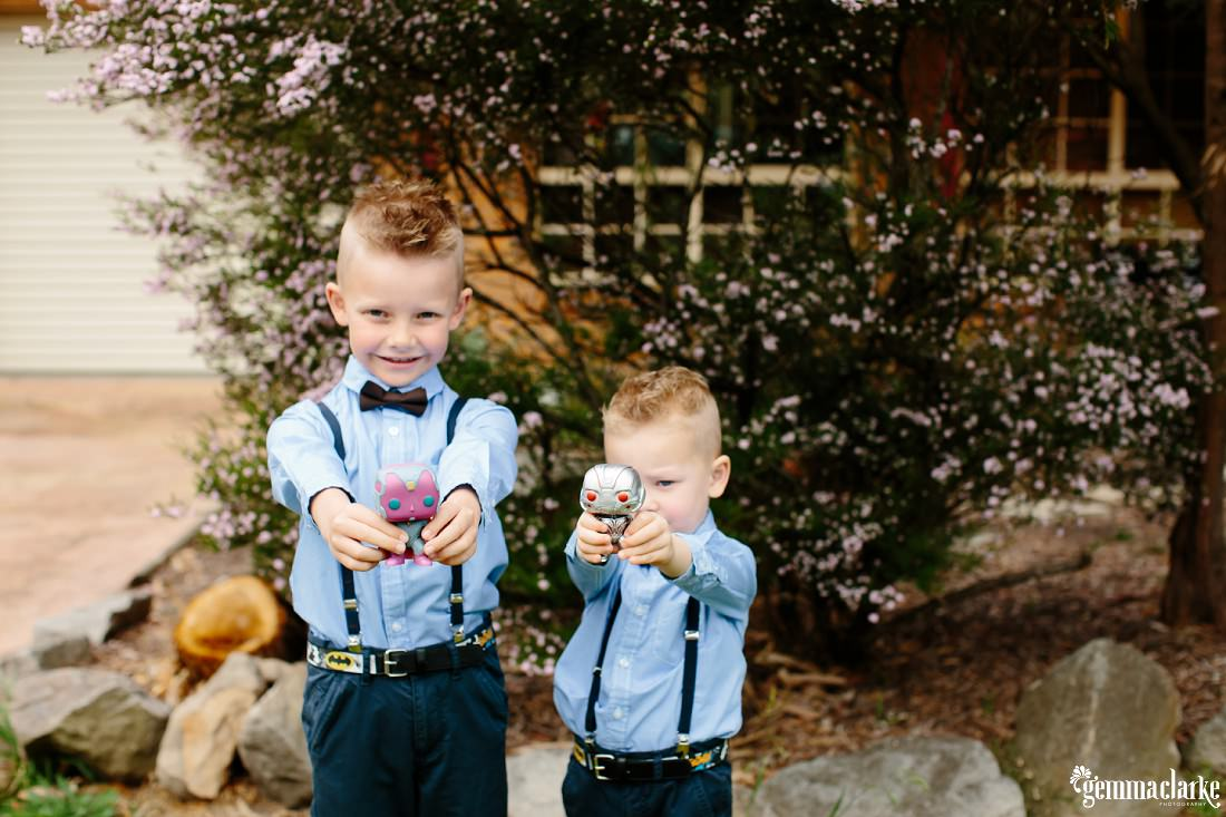 Two young boys in formal attire with blue shirts with navy pants, suspenders and bow ties smiling and holding small figurines