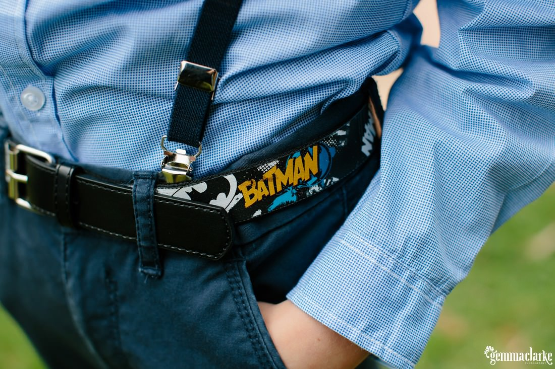 A close up of a young boy's Batman belt