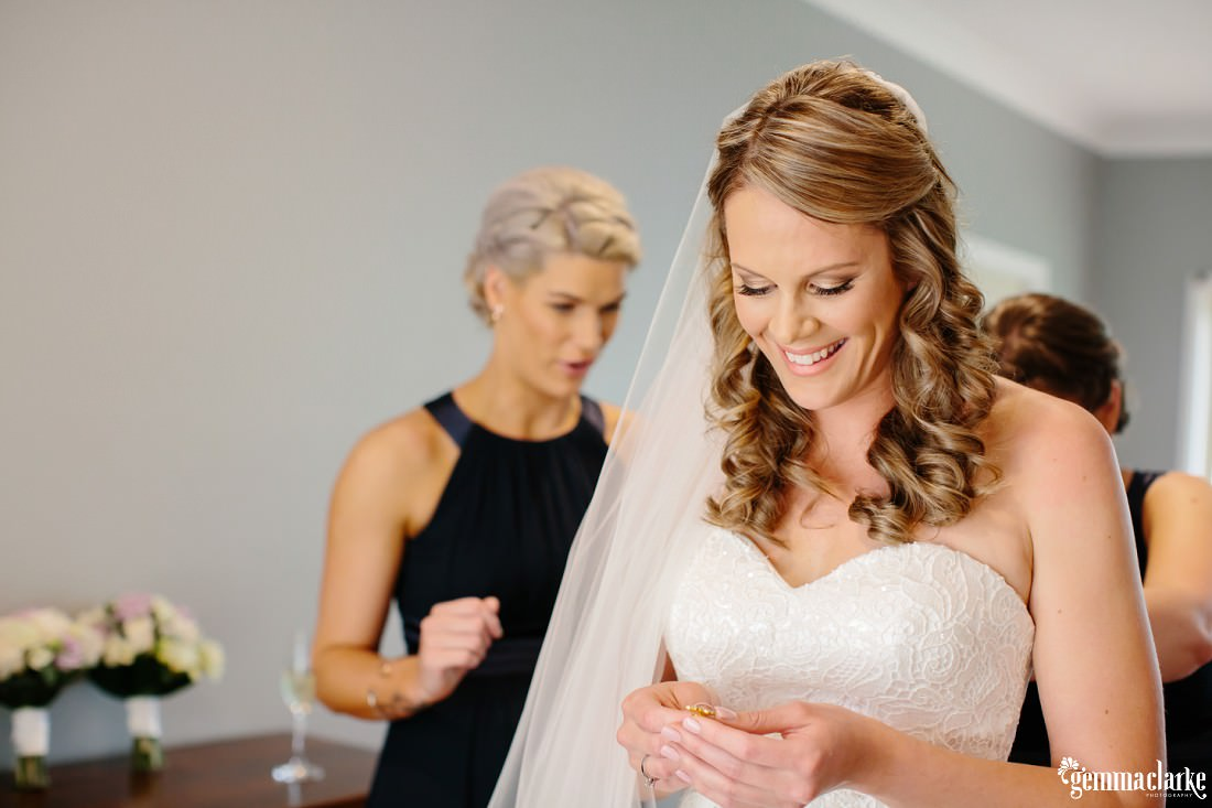 A bride smiling and looking at a decorative pin