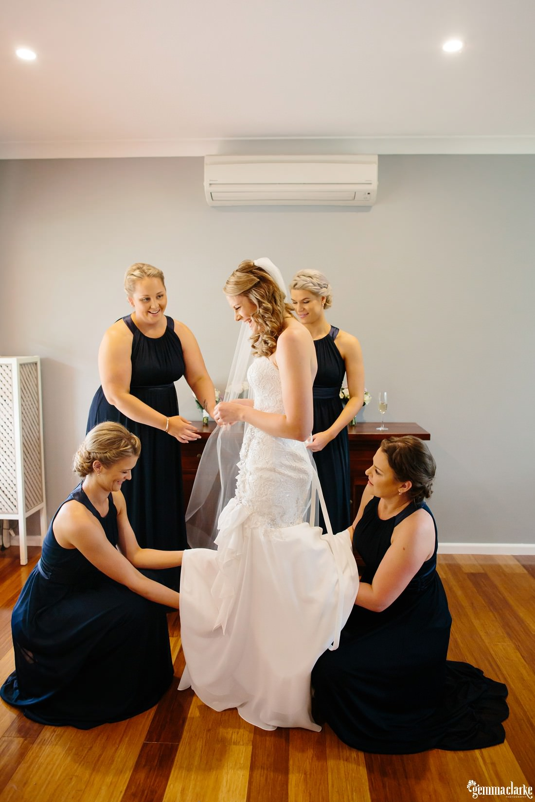 A smiling bride and her four bridesmaids helping her make final adjustments to her dress
