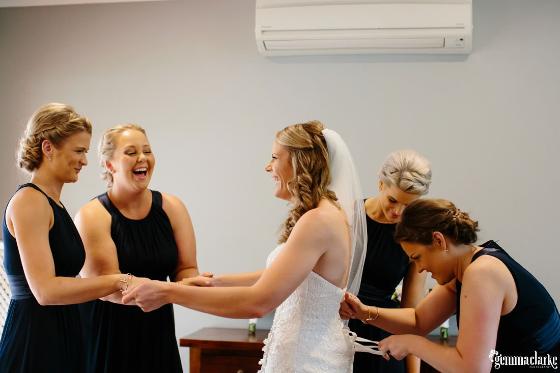 Four bridesmaids helping to tie up the bride's dress