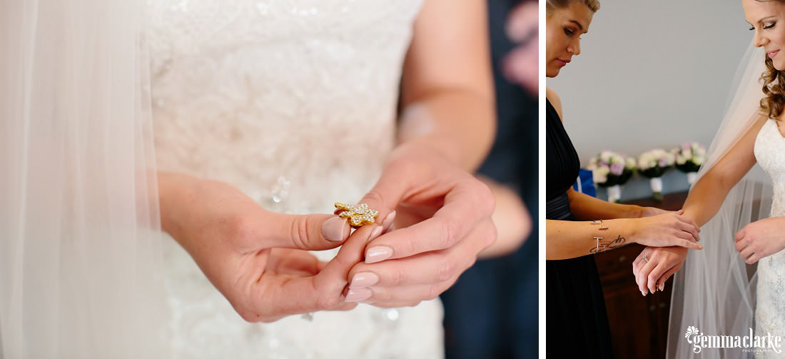 A bride holding a decorative pin and a bridesmaid helping her put on a bracelet