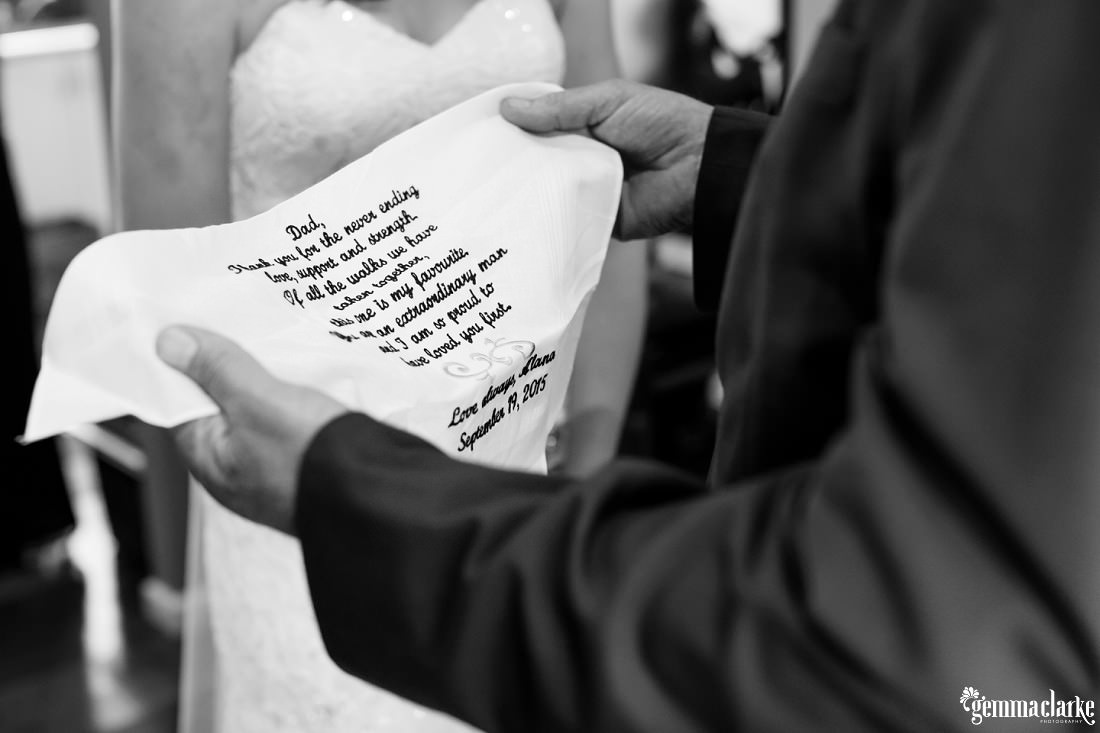 A bride's father holding a handkerchief embroidered with an emotional message from his daughter