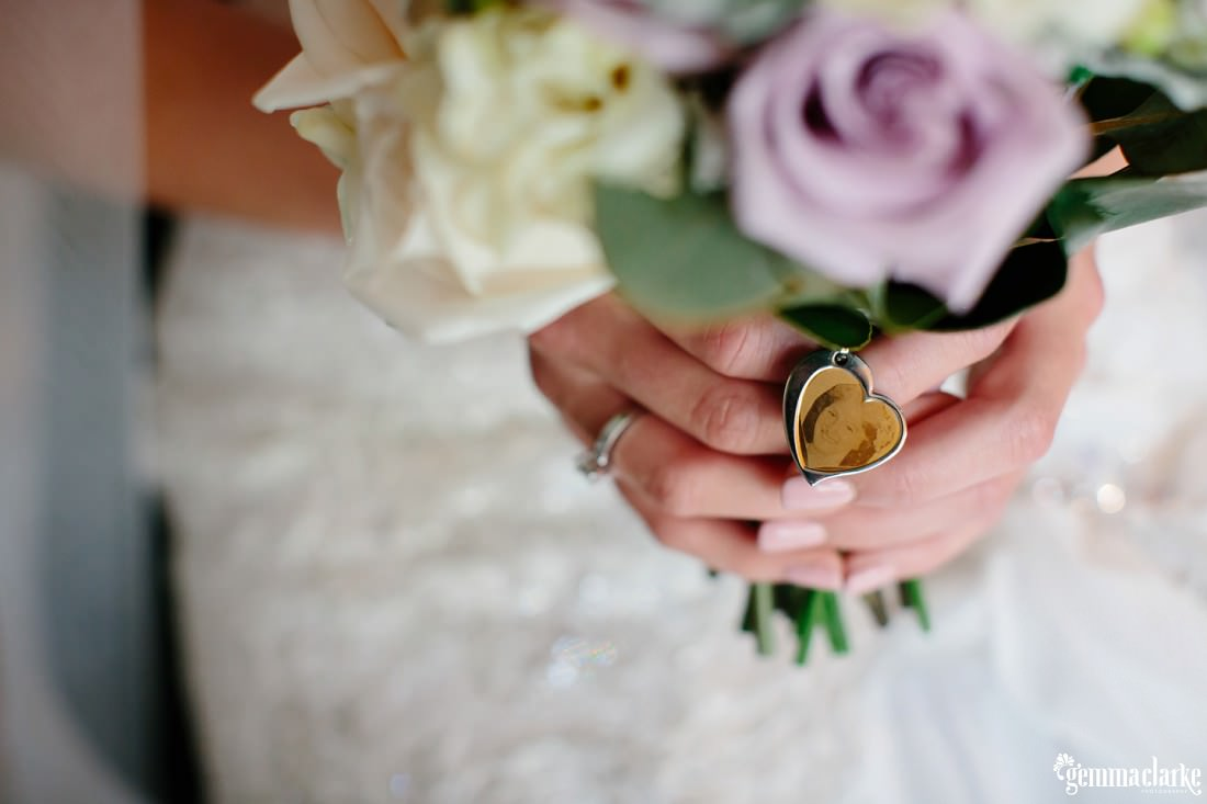 A photograph of the bride's mother in a love heart shaped locket attached to her bouquet