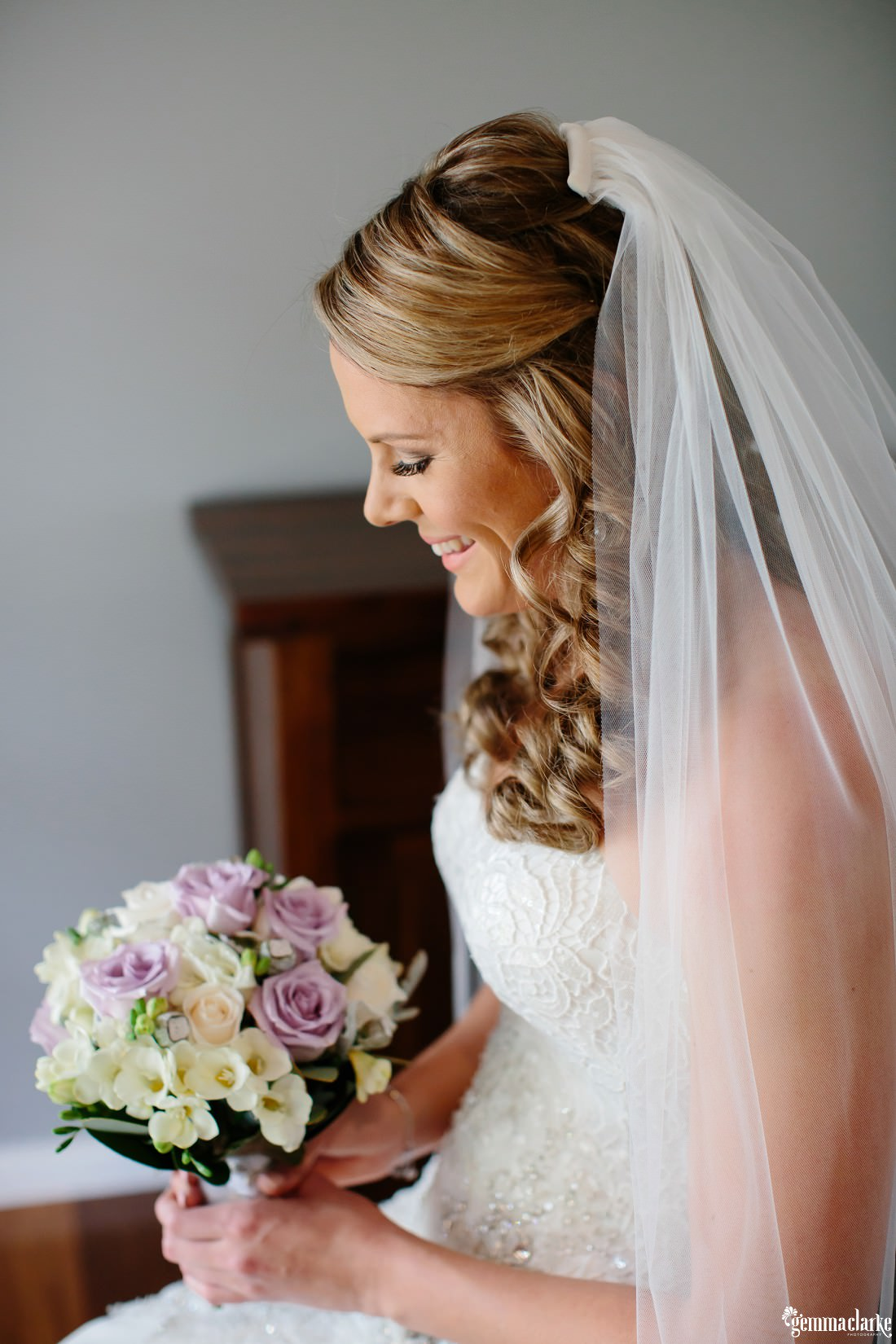 A bride smiling and looking at her floral bouquet