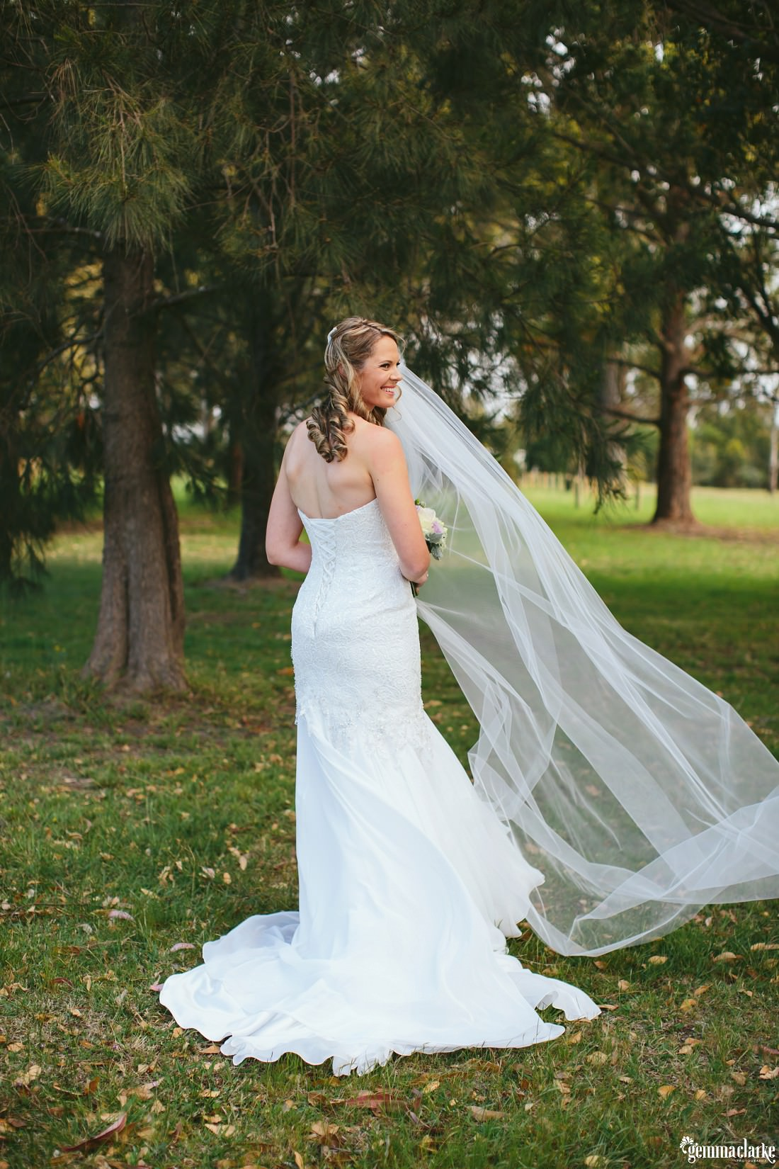 A bride posing in front of some trees, looking back over her shoulder and smiling
