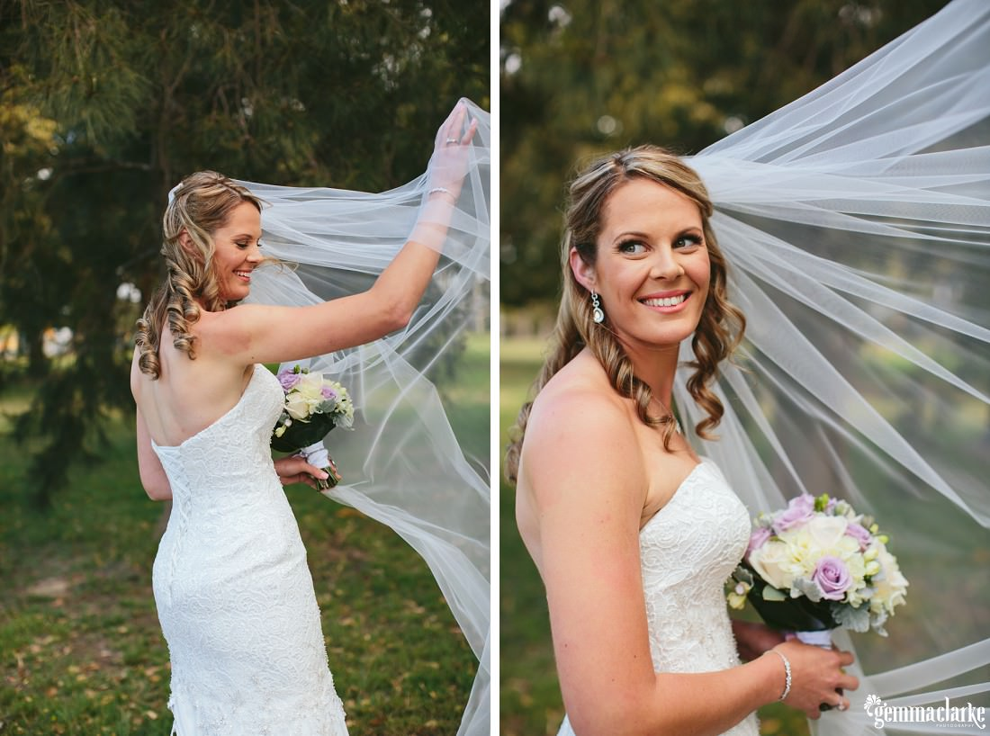A bride holding up her veil and smiling